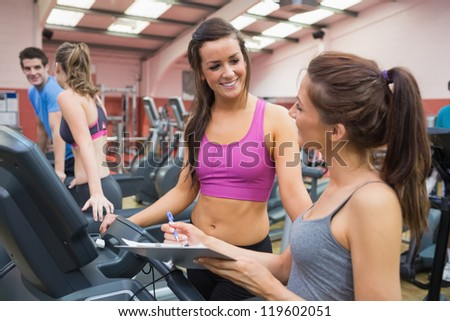 Women smiling in gym while carrying out assessment - stock photo