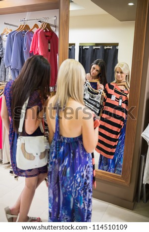 Women standing at the mirror holding up clothes in shopping mall - stock photo