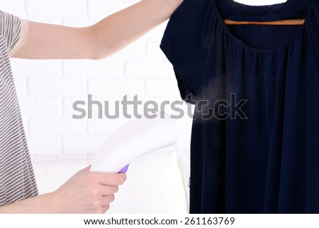 Women steaming dress in room - stock photo