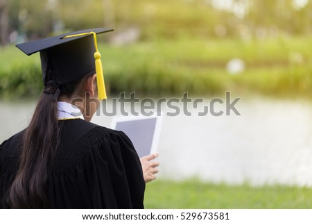 Women Student Graduate playing tablet in her hand feeling relaxing and so happiness in Commencement day