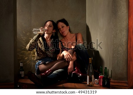 Women surrounded by booze bottles in a hallway