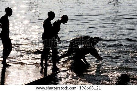 Women swimmers in Triathlon, starting the race, high contrast silhouetes - stock photo