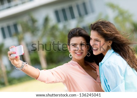 Women taking a picture of themselves with the mobile phone - stock photo