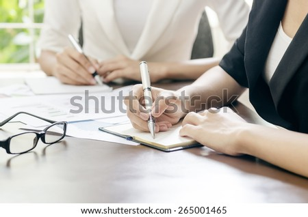 women taking note in a meeting