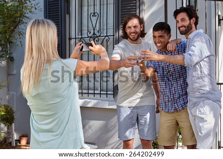 women taking photo pictures of group friends on mobile cellphone camera outdoors at garden party - stock photo