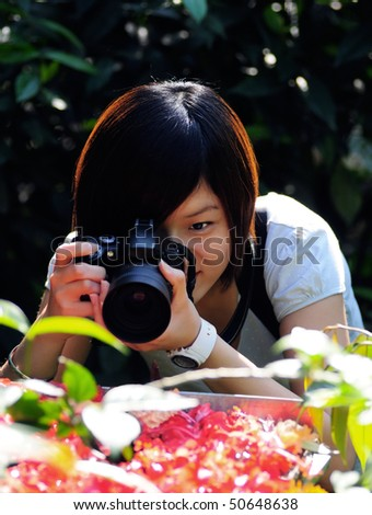 Women taking picture of flowers - stock photo
