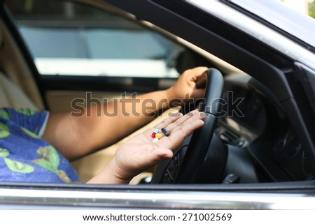 Women taking pills inside his car while driving - stock photo