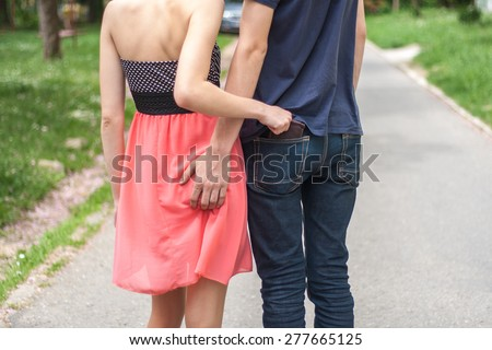 women taking wallet from man's pocket - stock photo