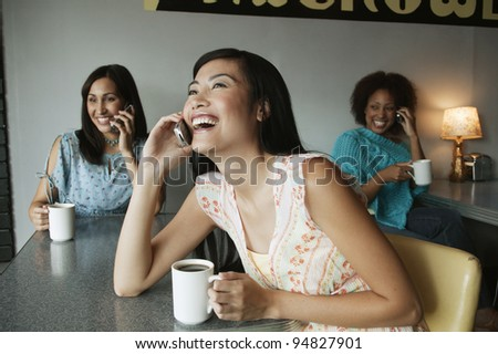 Women talking on cell phones in cafe - stock photo