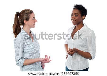 Women talking to each other, studio shot.