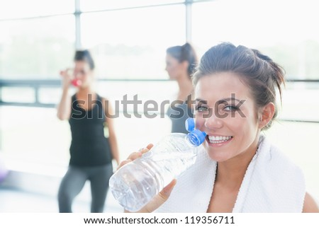 Women talking while another drinking water in fitness studio in gym - stock photo