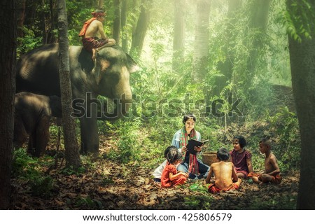 Women teacher teach children with elephant and mahout watching