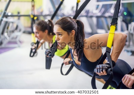 Women training arms with trx fitness straps in the gym doing push ups train upper body chest shoulders pecs triceps. - stock photo