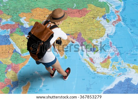 Women traveler Is planning a tour her standing on the world map.She points to the map