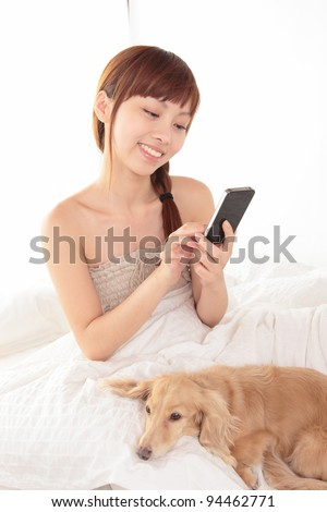 Women use a cell smart mobile phone on the bed - stock photo