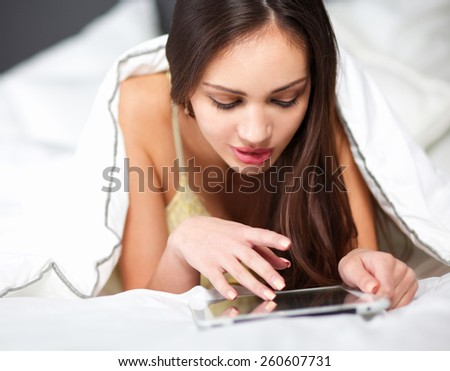 Women use a tablet pc on the bed - stock photo