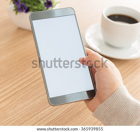 women using mobile phone in cafe. sofe focus. blank screen for your advertising. - stock photo