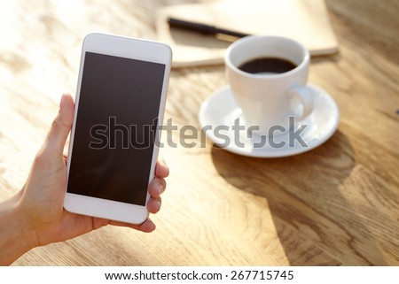 Women using smart phone, close-up, coffee and planning book on the background - stock photo