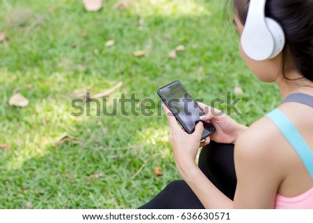 Women using smartphones, listening to music in the Park.