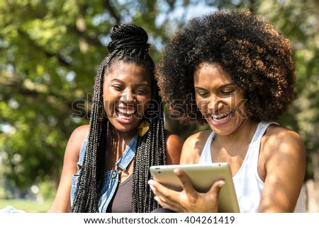 women using tablet computer in the park - stock photo