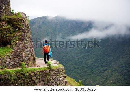 Women walking on the edge of a cliff, Machu Picchu, Peru - stock photo