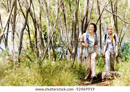 Women walking outdoor in the woods, happy exploring and adventure lies ahead for these wilderness trekking friends - stock photo
