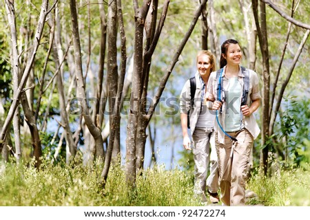 Women walking outdoor in the woods, happy exploring and adventure lies ahead for these wilderness trekking friends
