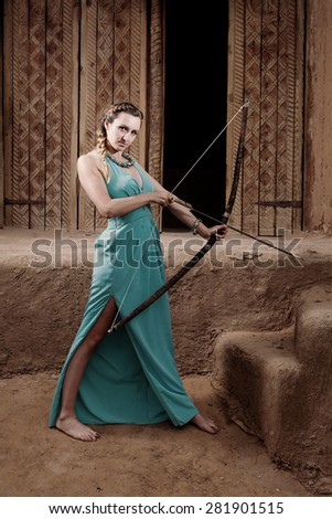 Women warrior with bow  looking at camera toned image. She is on ancient city background. - stock photo