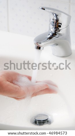 Women washes with running water and soap hands. Protection against the new flu infection.
