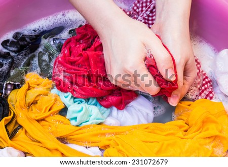 Women washing clothes in the enameled bowl - stock photo