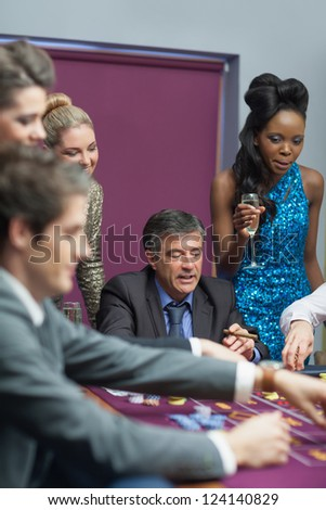Women watching men placing bes on roulette - stock photo