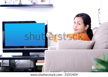 Women watching television - hand holding a TV remote - stock photo