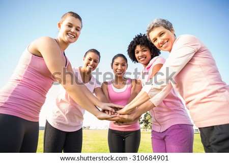 Women wearing pink for breast cancer and putting hands together in parkland - stock photo