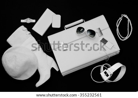 women white color accessories (sunglasses,suitcase,belt,necklace,mobile,watch,wallet,boot,hat) on a black background in plan - stock photo