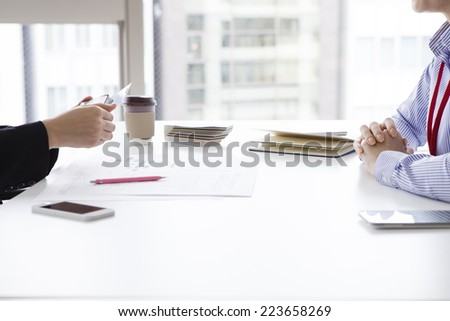Women who are trying to pass a business card - stock photo