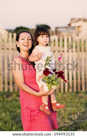 women with baby holding flowers in garden