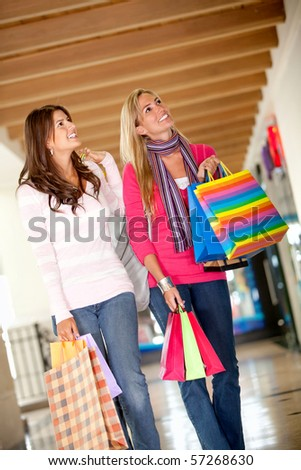 Women with bags walking at a shopping center  and smiling - stock photo