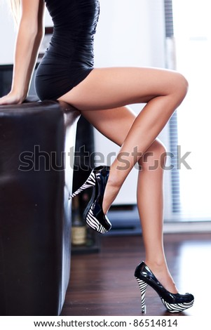 women with beautiful long legs sitting - stock photo