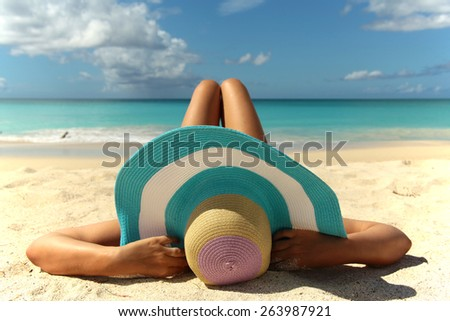 women with big colorful hat relaxing on the beach