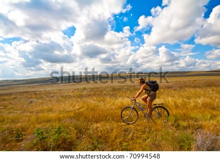 Women with bike on meadow - stock photo
