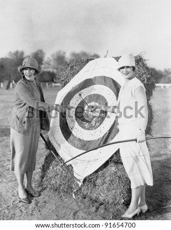 Women with bulls eye in archery target - stock photo