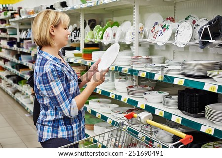 Women with cart shopping buys a plate in supermarket - stock photo