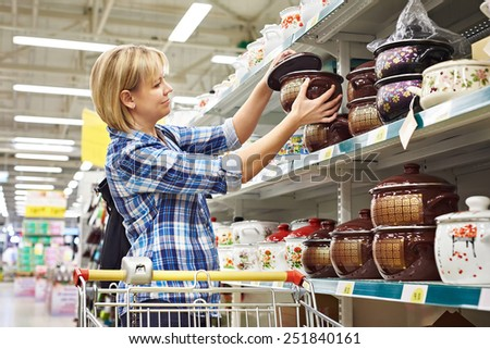 Women with cart shopping buys a saucepan in supermarket - stock photo