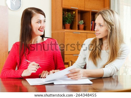 women with  documents  at table in home or office interior