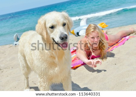 women with dog on the beach - stock photo