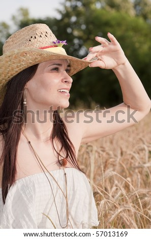 Women with hat in wheat field - stock photo