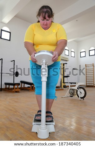 women with overweight standing on scales in the gym - stock photo