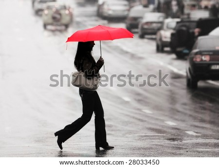 Women with red umbrella cross the street in the rain stock photo