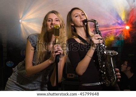 women with saxophone and microphone at concert