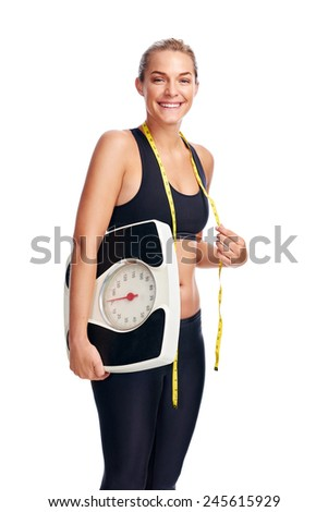 Women with scale cheering for achieving her weight loss goal isolated on white background - stock photo